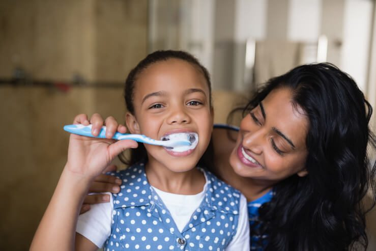 mom with daughter brushing her teeth
