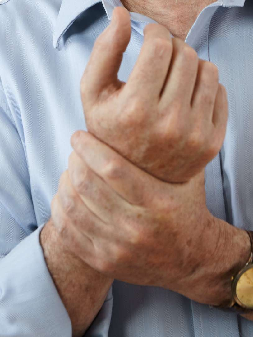 man holding wrist - hyperuricemia and gout section